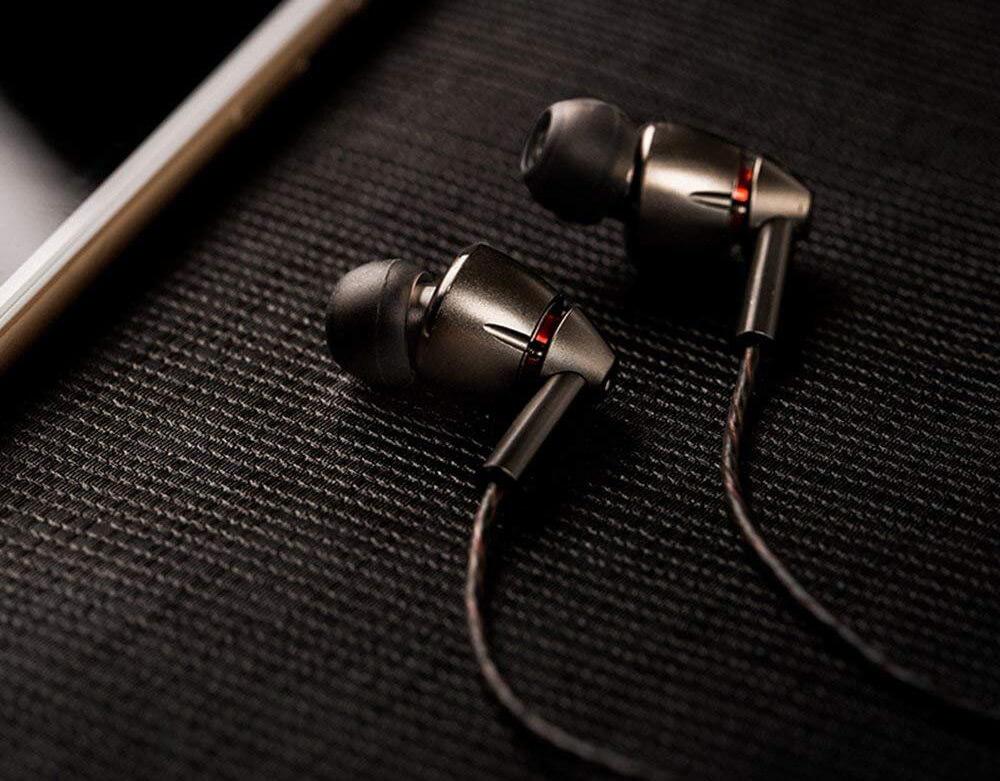 1MORE Quad-Driver Earbuds (E1010) next to phone