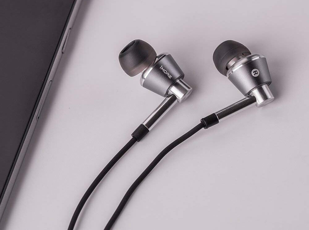 1MORE Triple-Driver Earbuds next to phone