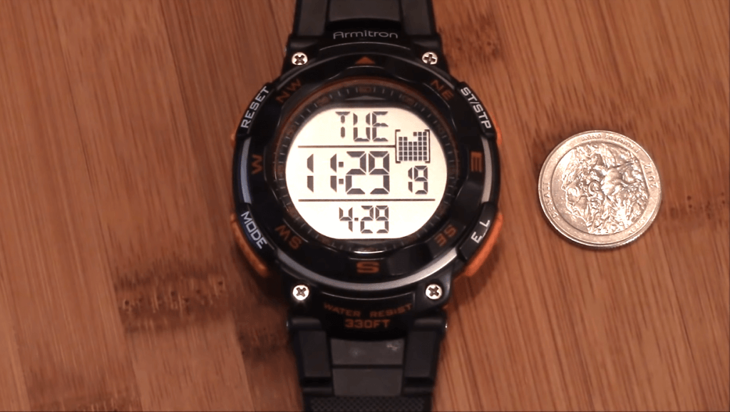 Armitron Sport 408254BLK next to coin comparison