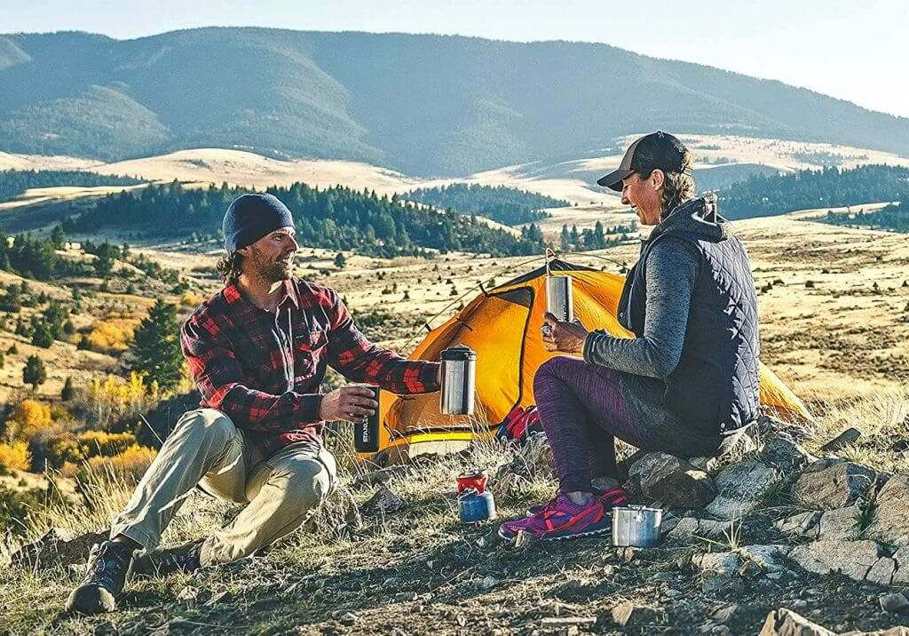 A couple using the Stanley Cook + Brew Camping Coffee Maker during a camping trip in the mountains