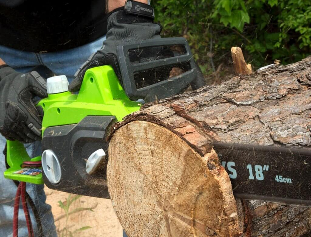 Greenworks 18-Inch Electric Chainsaw used for cutting a tree