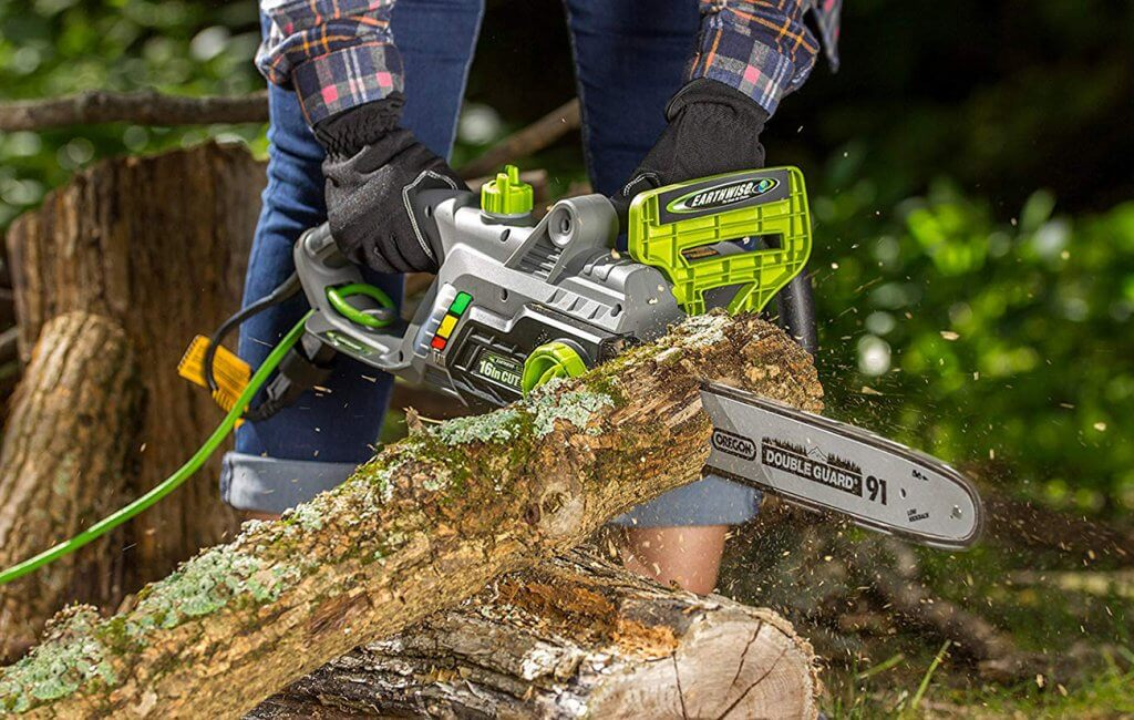 Someone using the Earthwise CS33016 Electric Chainsaw to cut a log