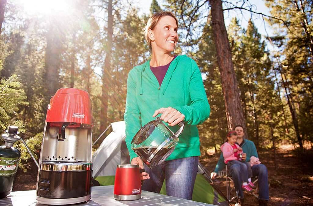 Woman making coffee on a camping trip with the Coleman QuikPot