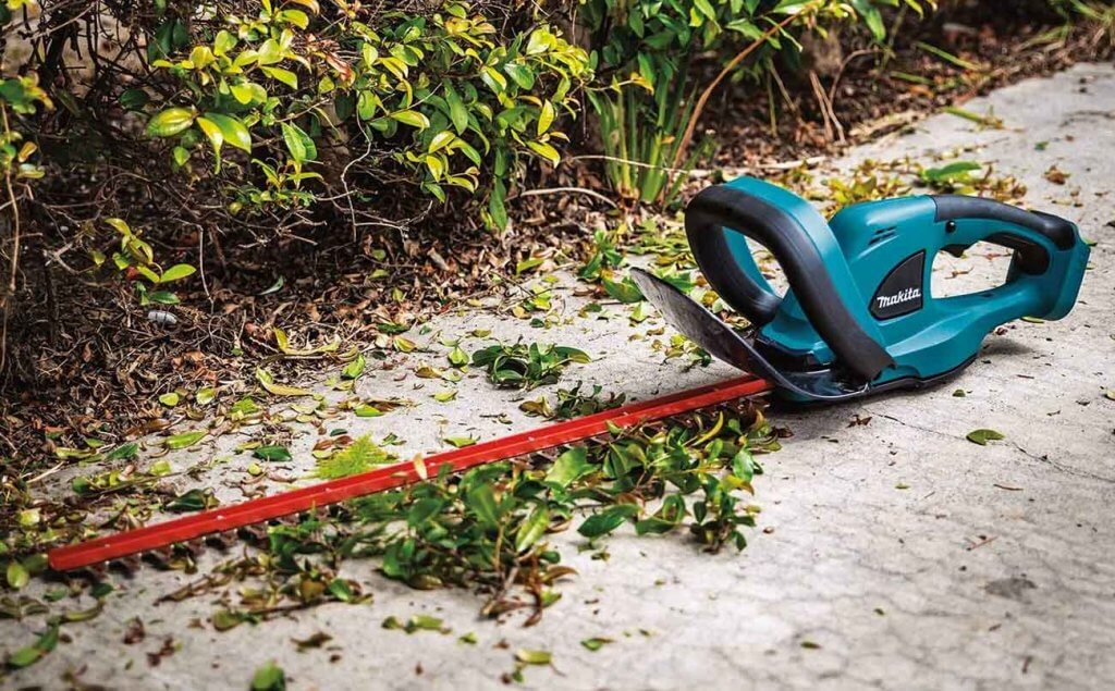 Makita XHU02Z Hedge Trimmer on the ground next to a hedge