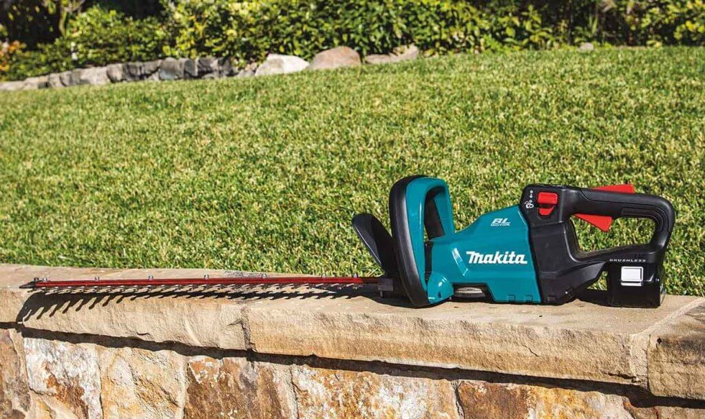 Makita XHU08T Hedge Trimmer on a garden wall
