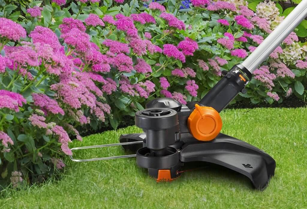 "WORX WG170 GT Revolution 20V 12"" cutting edge next to flowers"