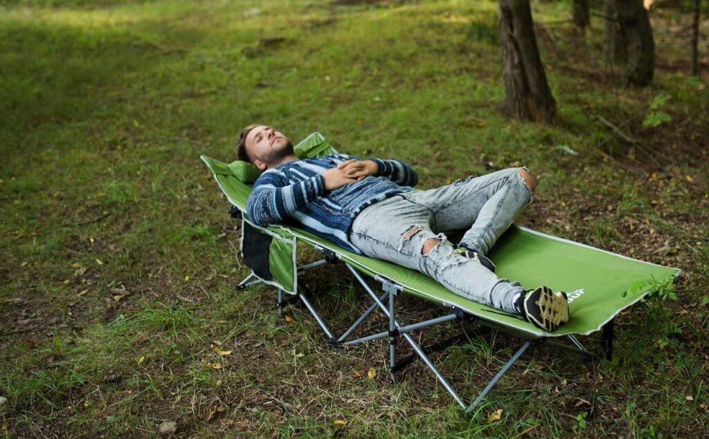 Someone sleeping on the Alpcour Folding Camping Cot