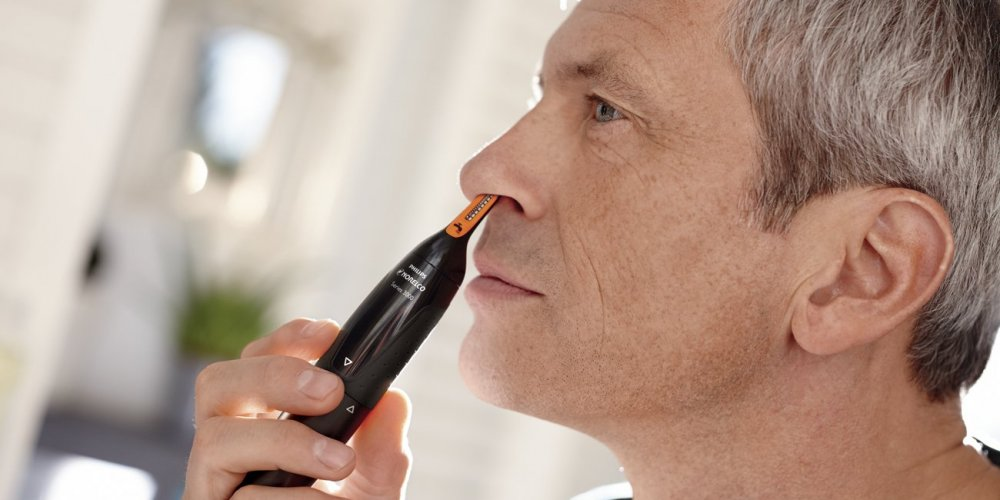 Men using a nose hair trimmer in front of the mirror