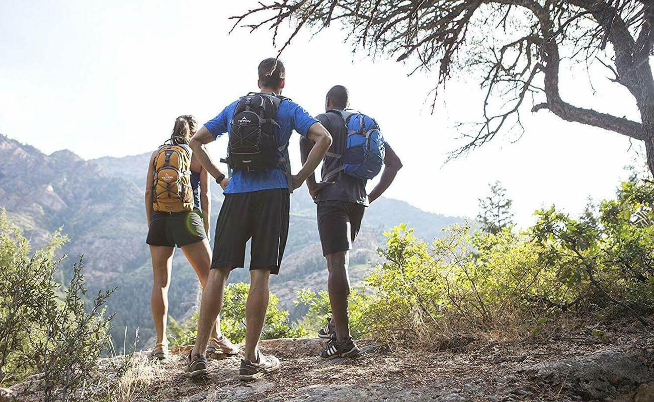 Three hikers wearing Hydration Packs