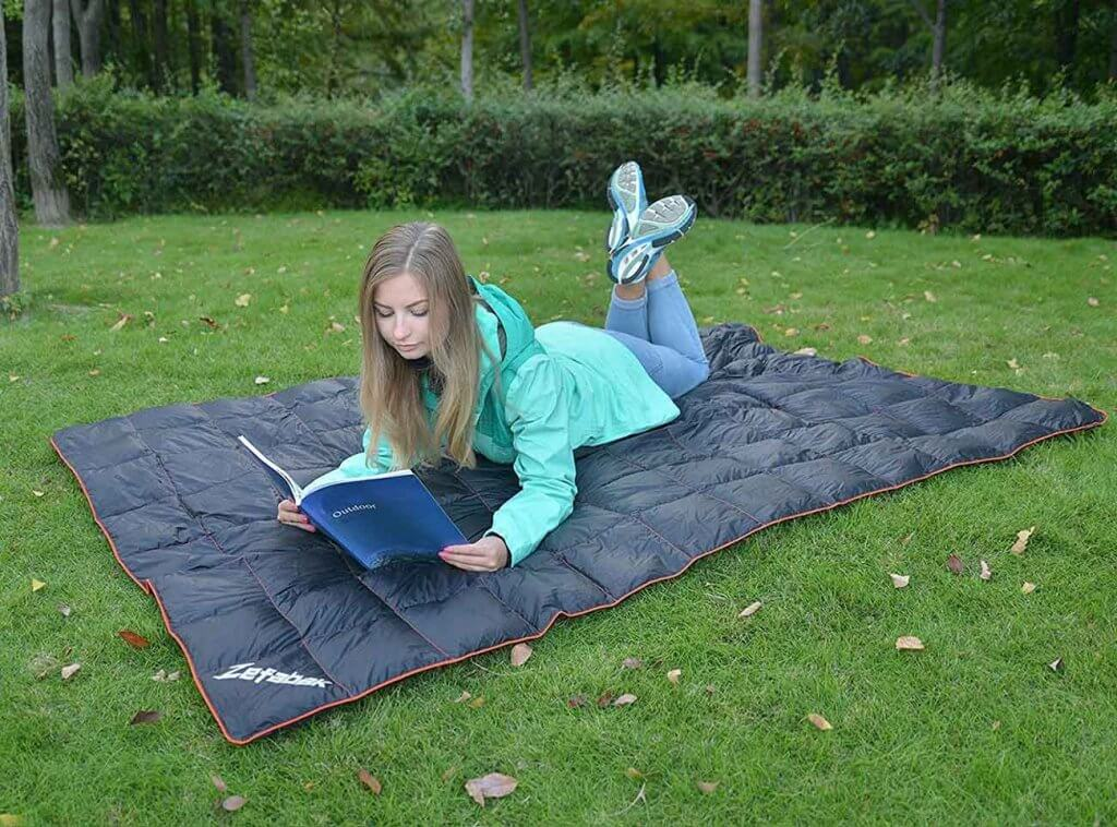 Girl reading a book on the Zefabak Camping Down Blanket